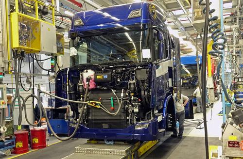 Takttijden bij Scania. Elke takttijd van circa 5 minuten verplaatsen de vrachtwagens zich